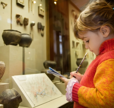 Child in museum taking notes
